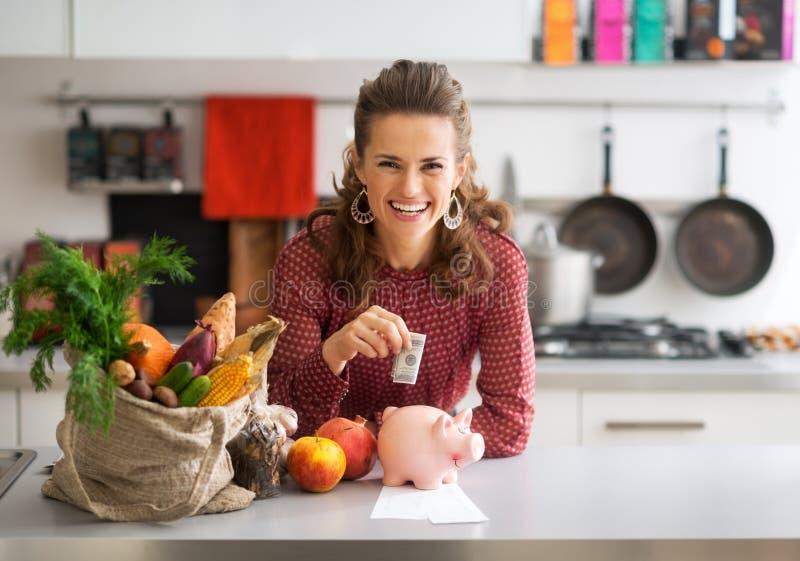 Gospodyni domowej kładzenia pieniądze w prosiątko banka obrazy royalty free