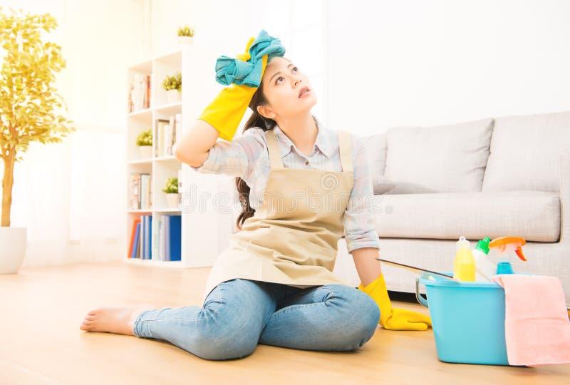 Gospodyni domowej odczucia zmęczony obsiadanie na podłoga zdjęcia stock