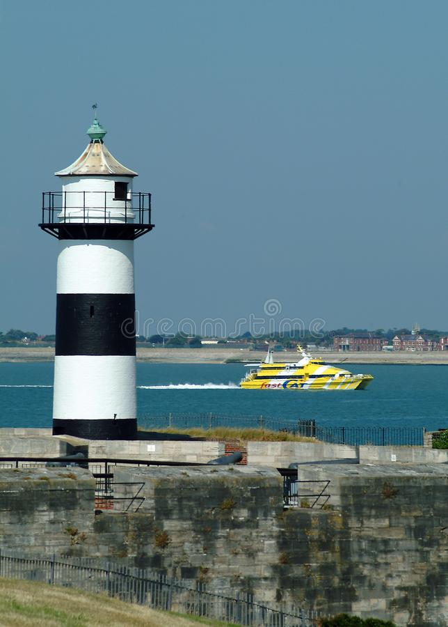 Catamaran and lighthouse. Gosport, United Kingdom - July 06 2004: A Wightlink FastCat ferry passes the Portsmouth Harbour lighthouse on it's way to the Isle of stock photography
