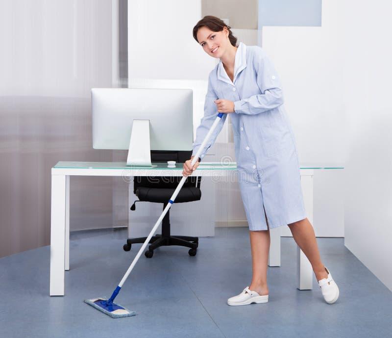 Gosposi cleaning podłoga w biurze obraz royalty free