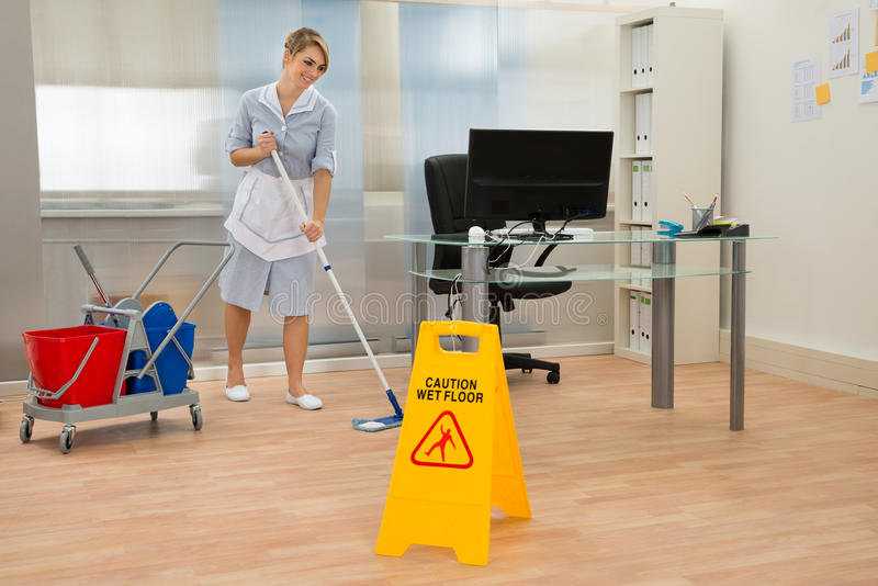 Gosposi cleaning podłoga w biurze zdjęcia stock