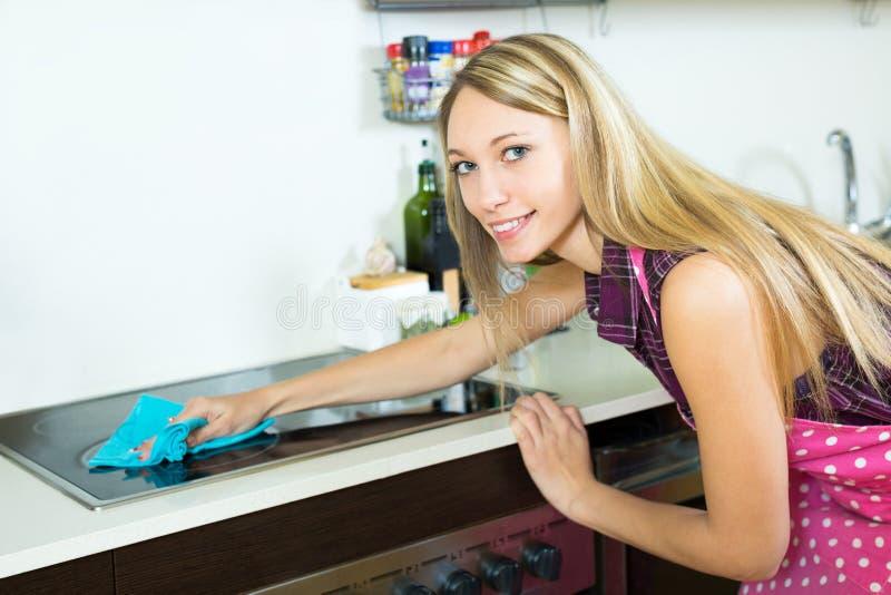 Gosposia czyści nowożytną kuchenkę zdjęcia stock