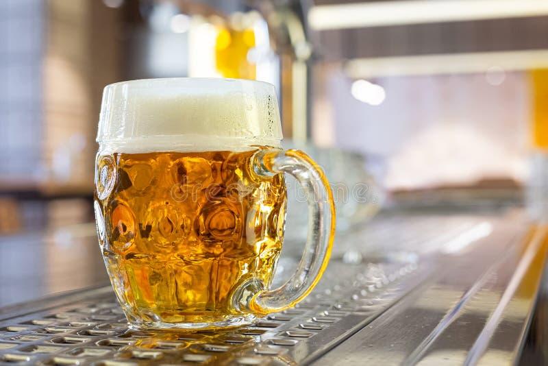 Goss frisch EntwurfsLager-Bier in einem Grübchen gebildeten Glasbecher auf Edelstahlzähler in einer modernen Kneipe Raum f?r Text lizenzfreie stockfotos