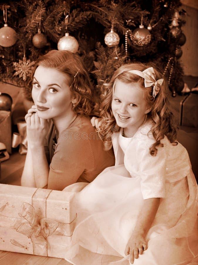 Gosse avec la mère près de l'arbre de Noël. photo stock