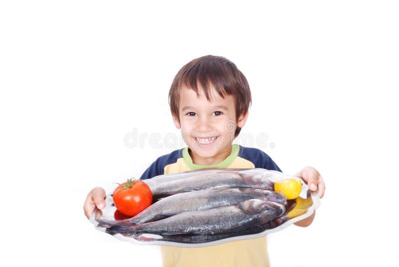 Gosse de sourire avec les poissons frais sur la table photo libre de droits