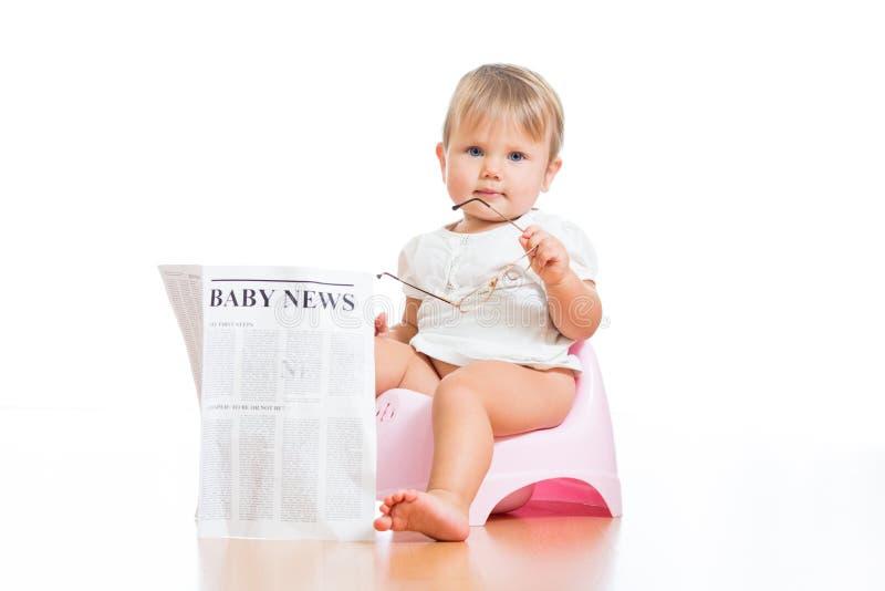 Gosse drôle s'asseyant sur le chamberpot avec le journal photographie stock libre de droits