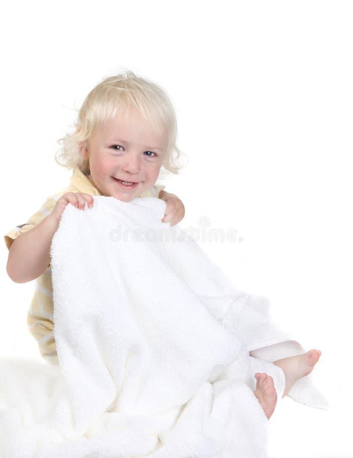 Gosse espiègle retenant un sourire d'essuie-main de Bath photographie stock libre de droits