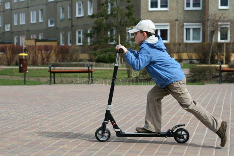 Gosse et scooter photographie stock