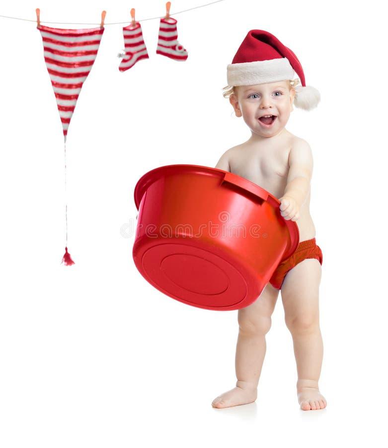 Gosse heureux dans le chapeau de Santa lavant ses accessoires photos stock