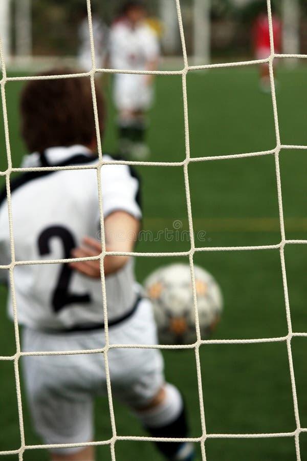 Gosse jouant au football image libre de droits