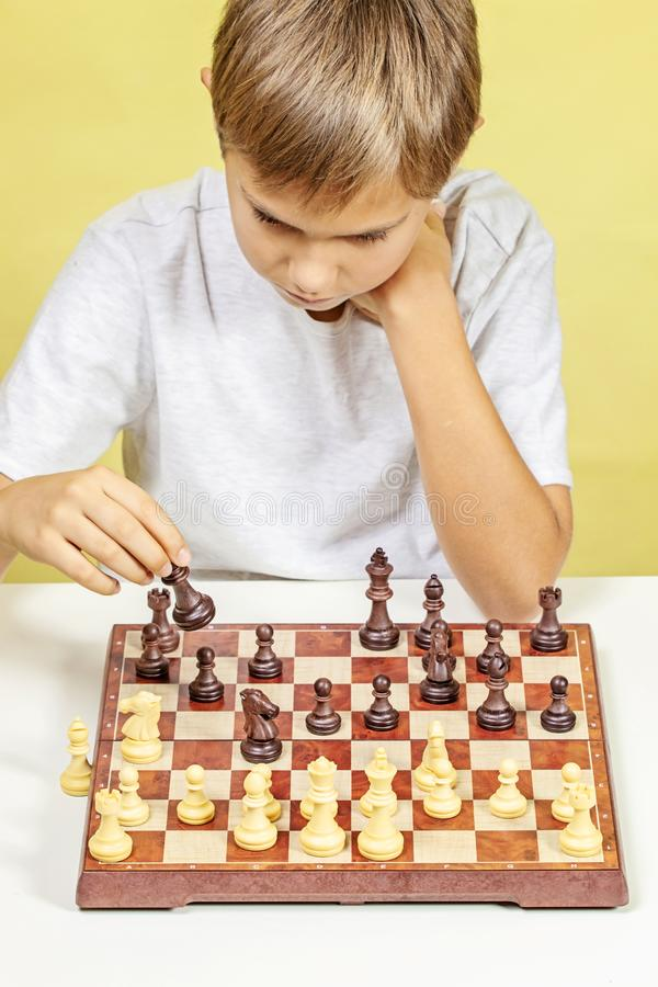 Gosse jouant aux échecs Garçon regardant l'échiquier et pensant à sa stratégie photos stock
