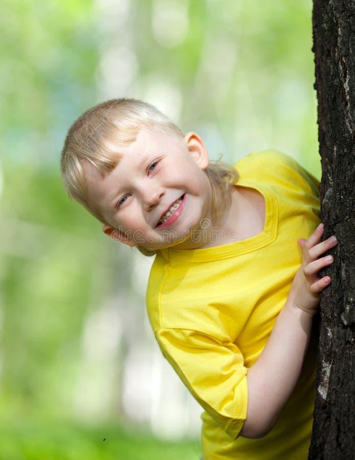 Gosse jouant sur l'arbre de stationnement extérieur photo libre de droits