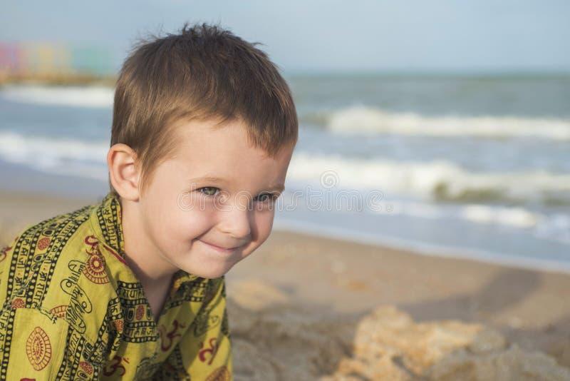 Gosse jouant sur la plage Jeu mignon de petit garçon avec le sable sur la plage images libres de droits