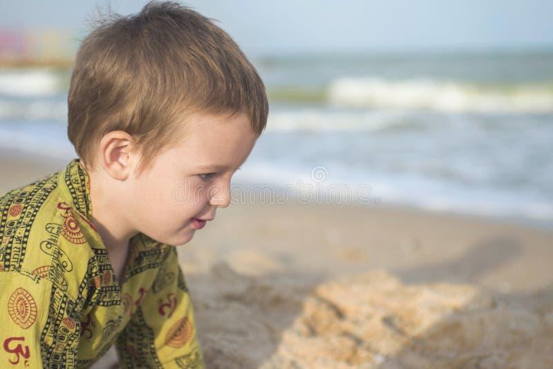 Gosse jouant sur la plage Jeu mignon de petit garçon avec le sable sur la plage image stock