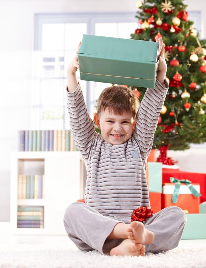 Gosse mignon soulevant la haute de cadeau de Noël photos stock