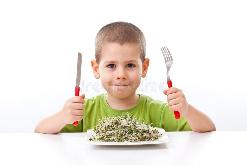 Gosse prenant la nourriture verte images stock