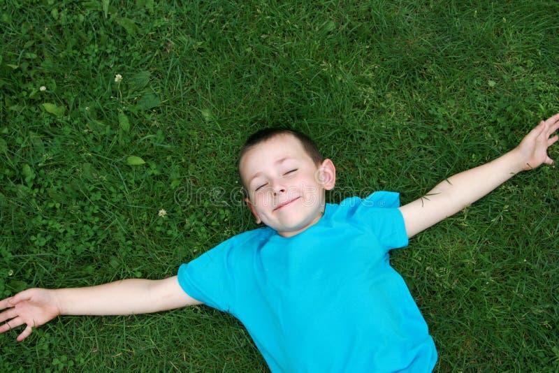Gosse se trouvant sur l'herbe photo libre de droits