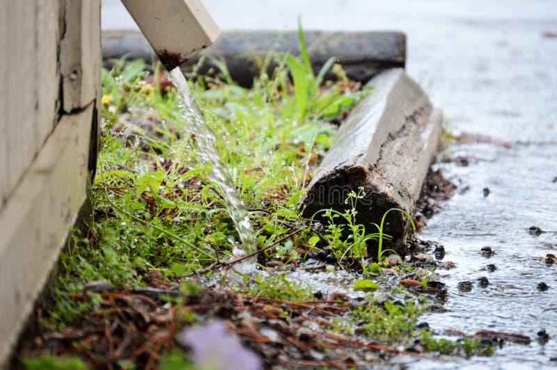 Gosse spuckt Regenwasser lizenzfreies stockbild