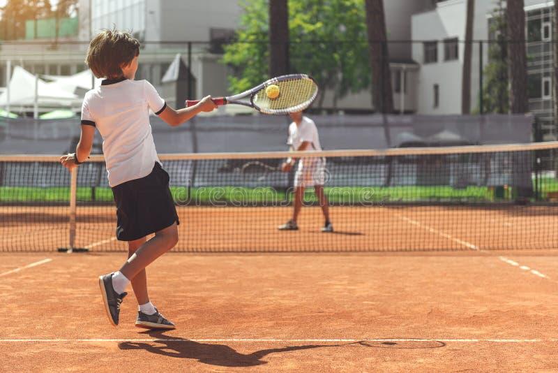 Gossebarn som spelar tennis med motståndaren royaltyfria foton