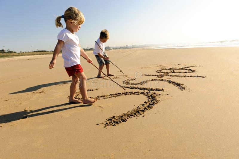 Gosses écrivant en sable photographie stock