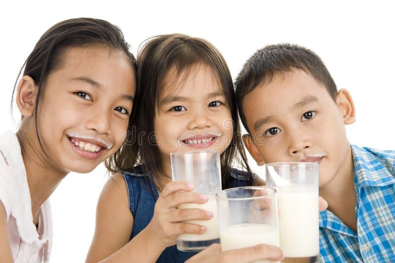 Gosses asiatiques avec du lait images libres de droits