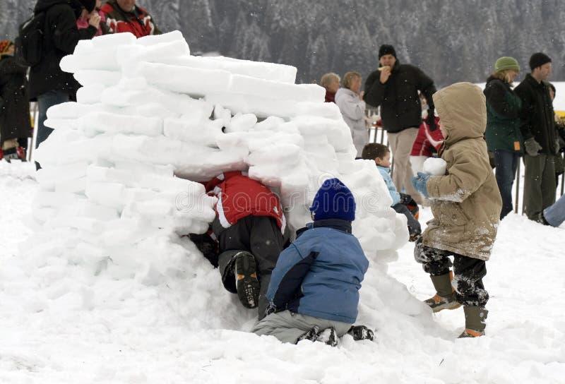 Gosses construisant un igloo (maison de neige) images stock