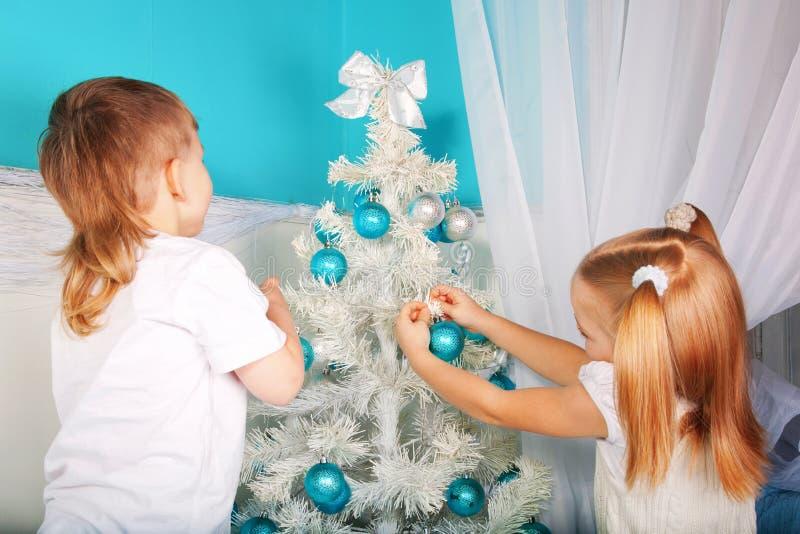 Gosses décorant l'arbre de Noël image stock