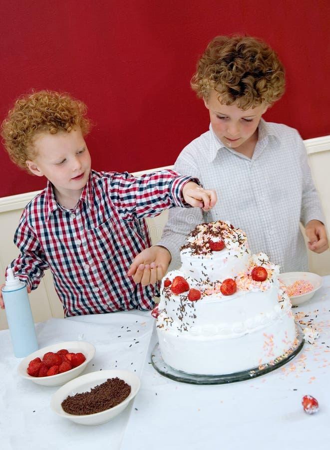 Gosses décorant le gâteau images libres de droits