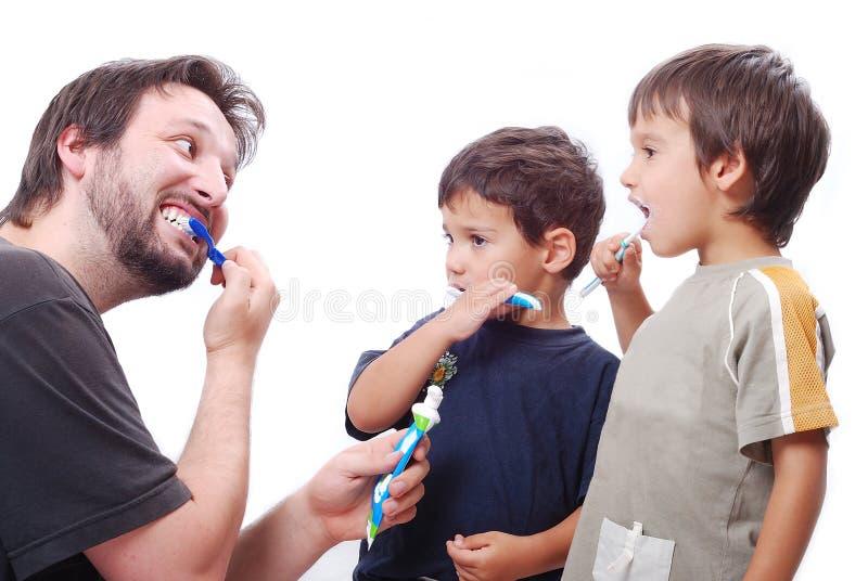 Gosses de enseignement de jeune homme comment nettoyer les dents photos libres de droits