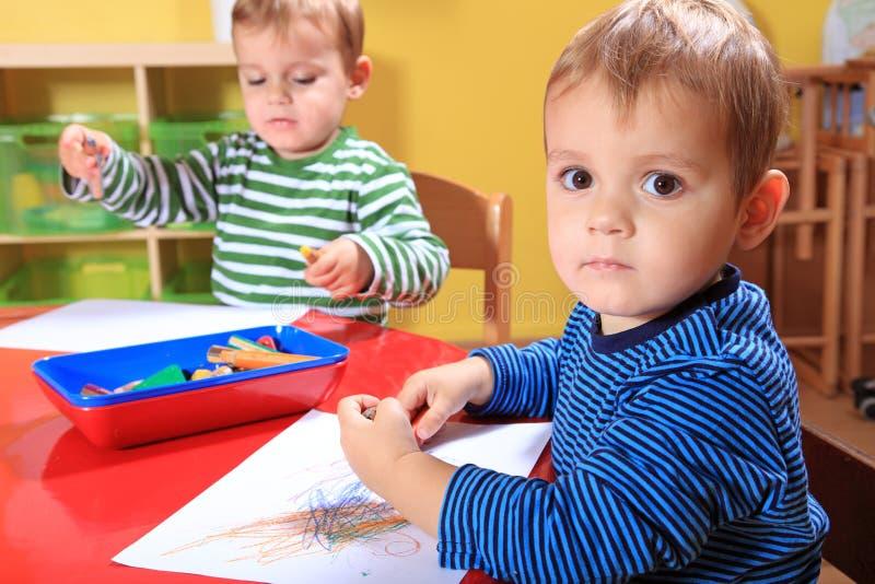 Gosses dessinant des illustrations dans le jardin d'enfants photos stock