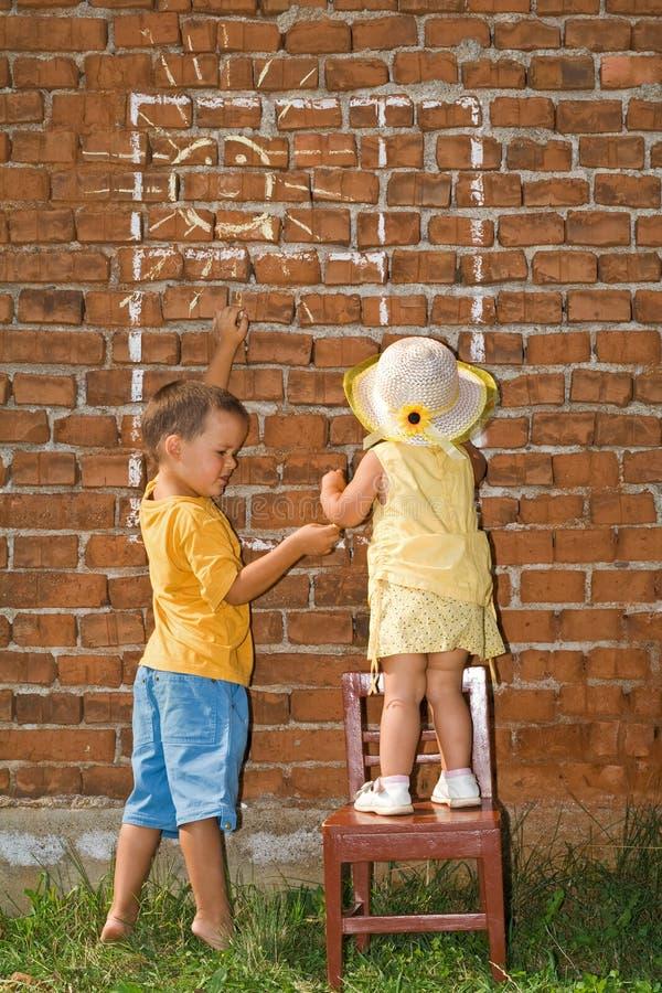 Gosses dessinant l'hublot ensoleillé à un mur de briques photos libres de droits