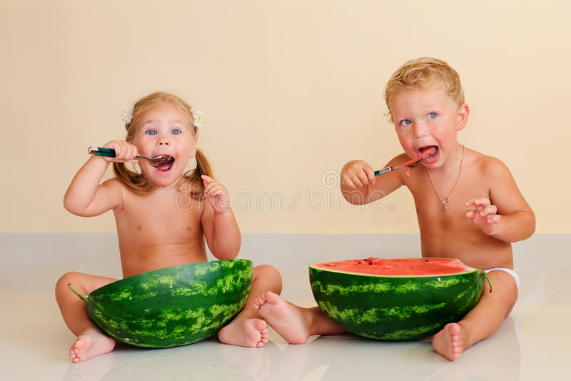 Gosses drôles mangeant la pastèque image libre de droits