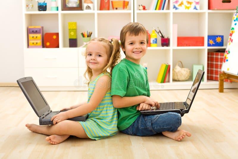 Gosses heureux avec des ordinateurs portatifs se reposant sur l'étage photographie stock libre de droits