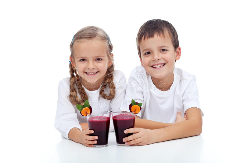 Gosses heureux avec le jus de légumes rouge frais image libre de droits