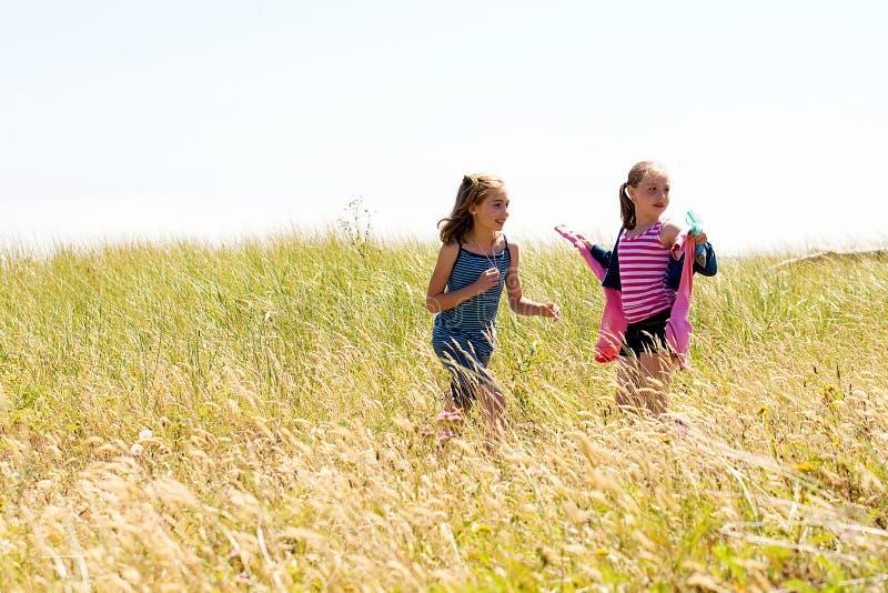 Gosses jouant dans un domaine d'herbe grande photo libre de droits