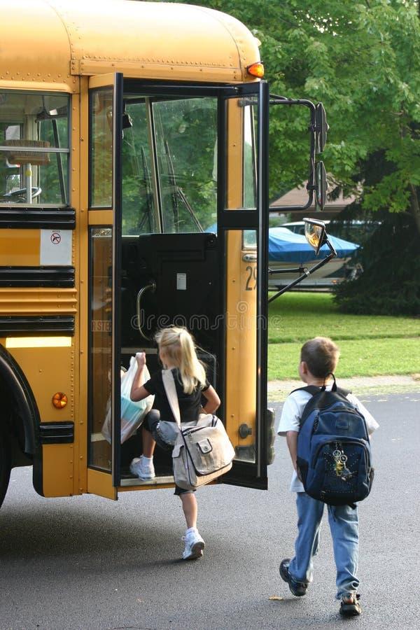 Gosses montant dans le bus image libre de droits