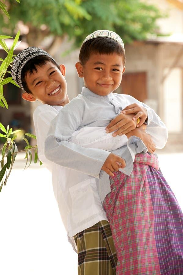Gosses musulmans heureux espiègles, amitié image stock