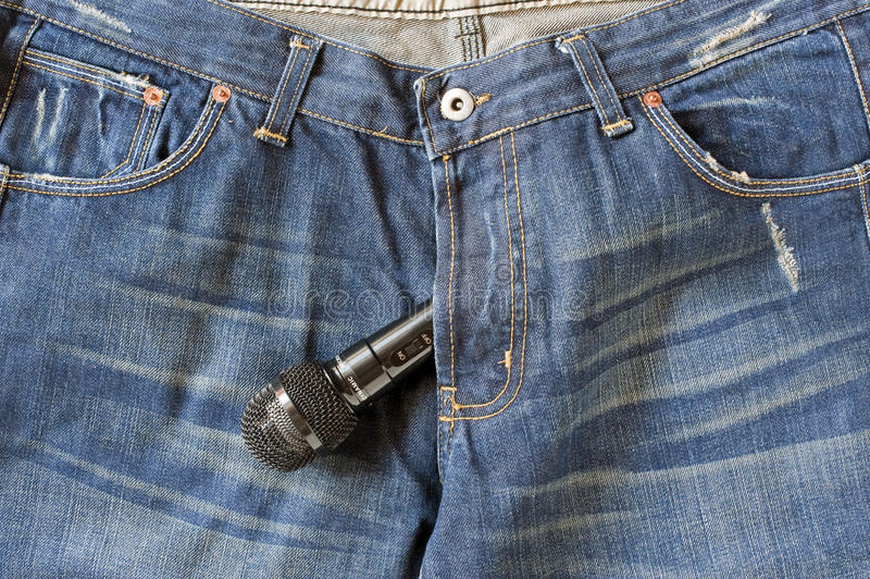 Gossip. Blue-jeans with a Microphone bulging out the zipper royalty free stock image