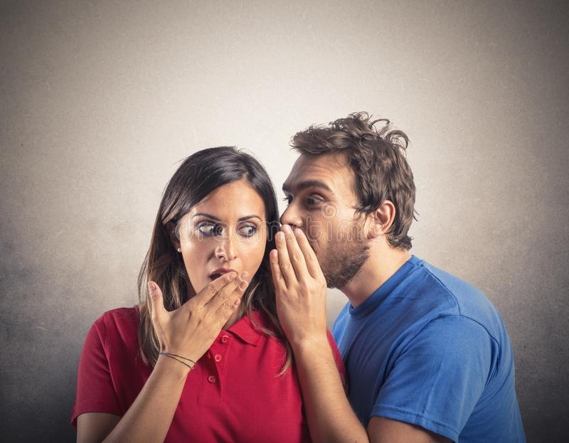 Gossip. Concept of gossip with boy whispers girl royalty free stock images