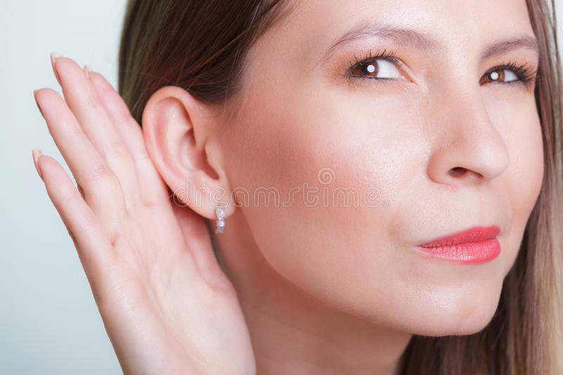 Gossip girl eavesdropping with hand to ear. royalty free stock photo