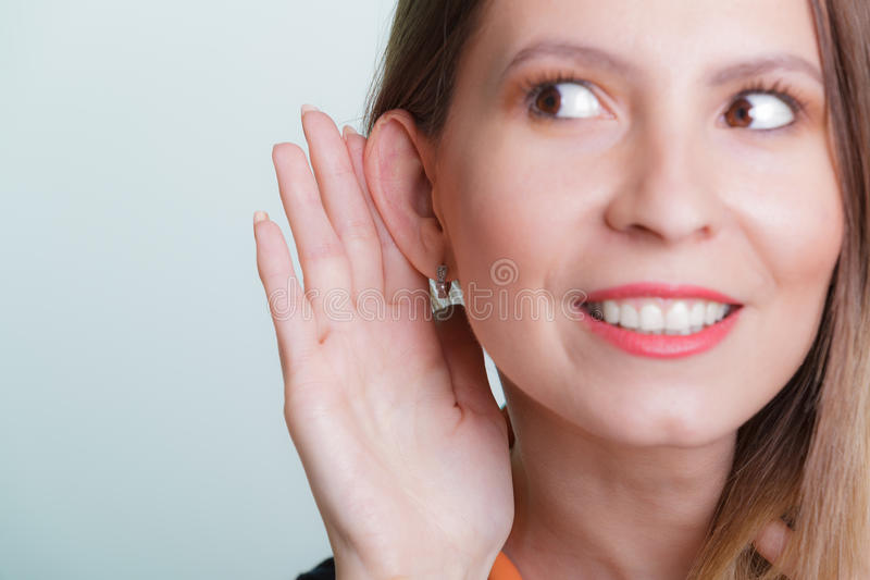Gossip girl eavesdropping with hand to ear. royalty free stock photography