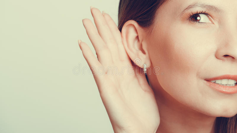 Gossip girl eavesdropping with hand to ear. stock images