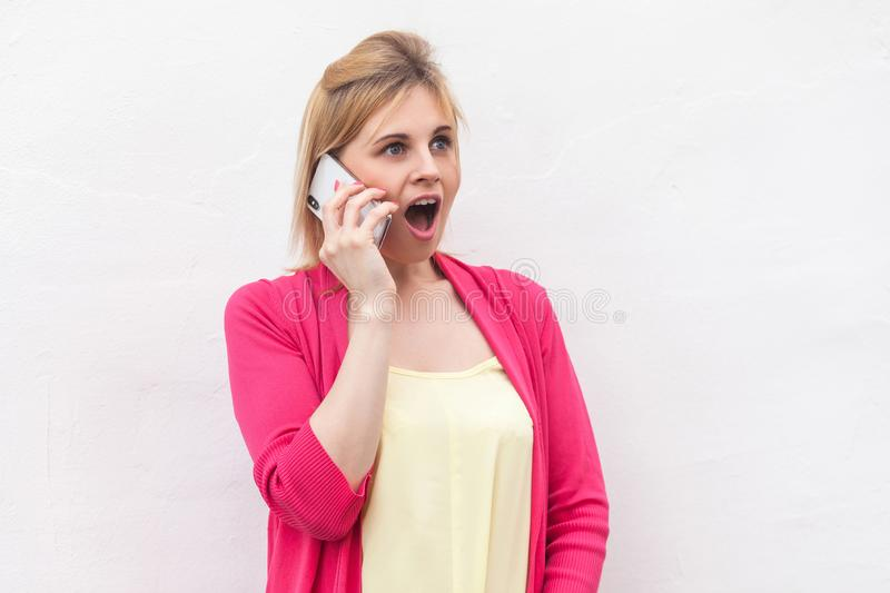 Gossip girl! Portrait of exited young woman in pink blouse standing, using and making call on her smartphone with wondering face royalty free stock images