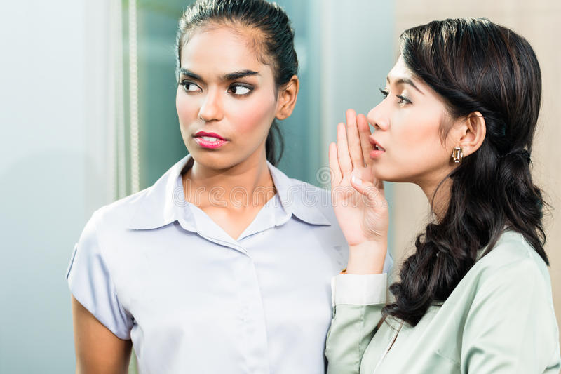 Gossip in the office, woman whispering in ear royalty free stock image
