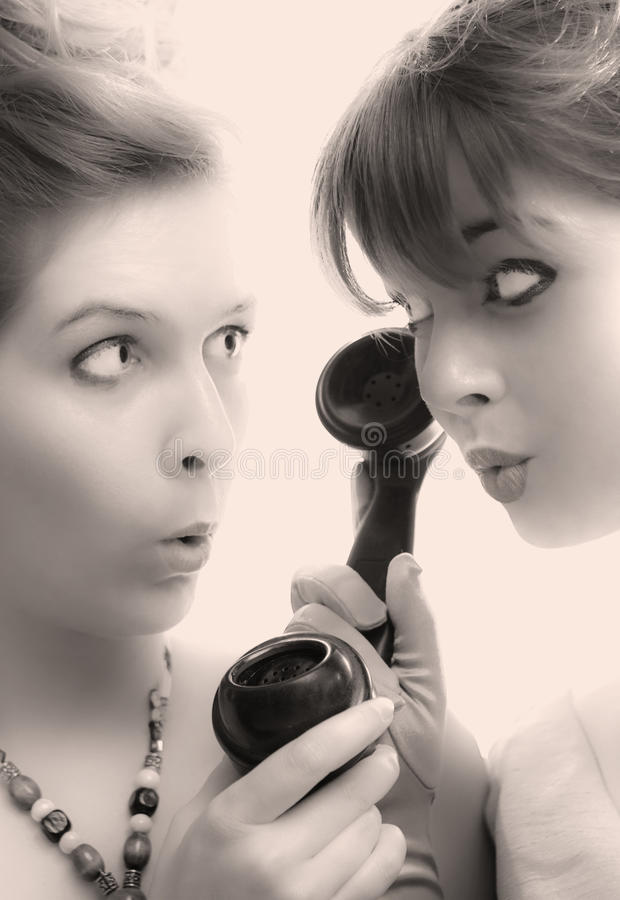 Gossip Queens. Couple of busy bodies eavesdropping royalty free stock photo