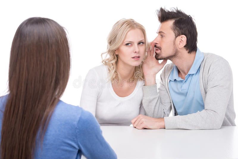Gossip. Two young people are gossip about their friend on white studio background stock image