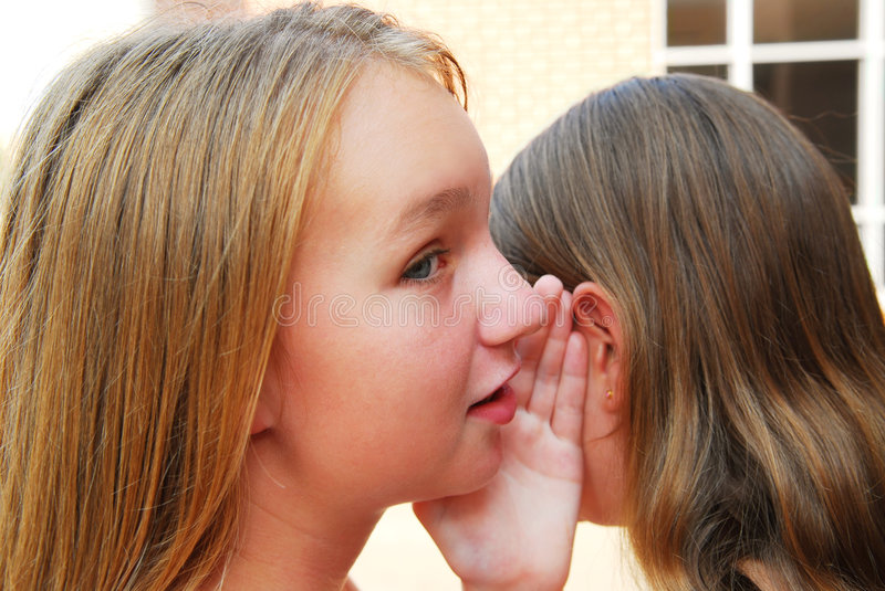 Gossiping. Two young teenage girls gossiping in school yard royalty free stock photography