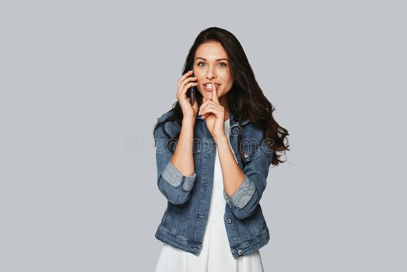 Gossiping. Attractive young woman talking on the phone and smiling while standing against grey background stock photo