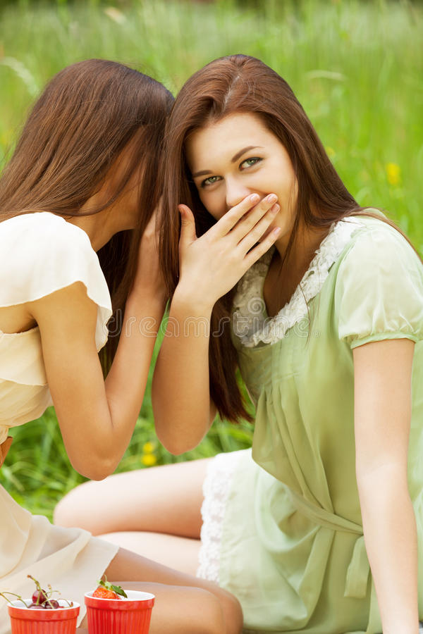 Gossips. Two cute girls gossiping outdoors royalty free stock photo