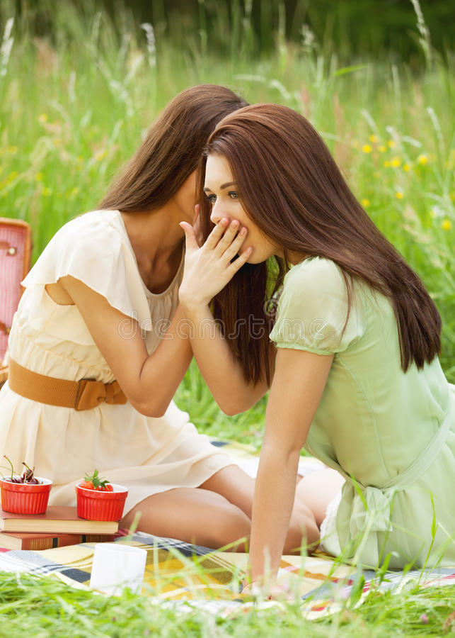 Gossips. Two girl gossiping during picnic stock photography